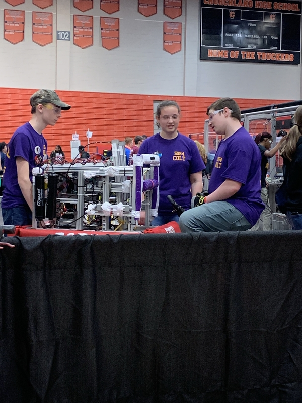 Members of the team work on the robot.